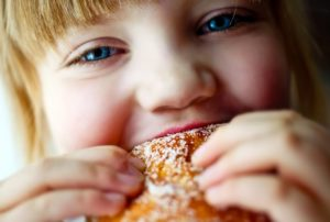 blonde girl biting into dessert