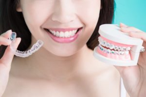 Woman holding Invisalign and fake teeth with braces
